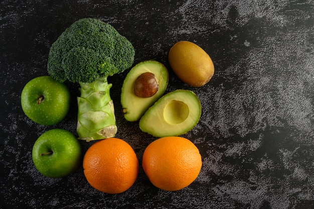Broccoli, mela, arancia, kiwi e avocado su un pavimento di cemento nero. Foto Gratuite