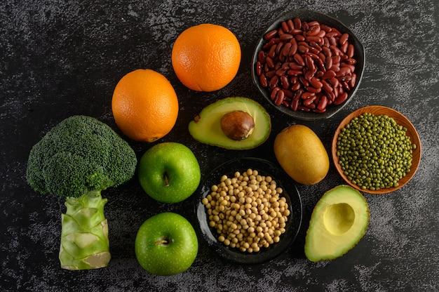 Broccoli, mela, arancia, kiwi, legumi e avocado su un pavimento di cemento nero. Foto Gratuite