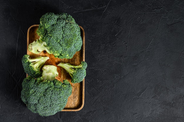 Broccoli verdi crudi su una ciotola di legno Foto Premium