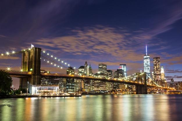 Brooklyn bridge e downtown skyscrapers a new york di notte Foto Premium