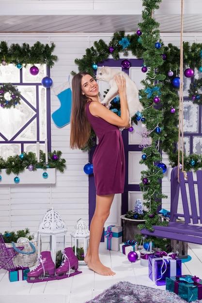 Bruna dalle gambe lunghe in un abito bordeaux seduto su un tappeto viola Foto Premium