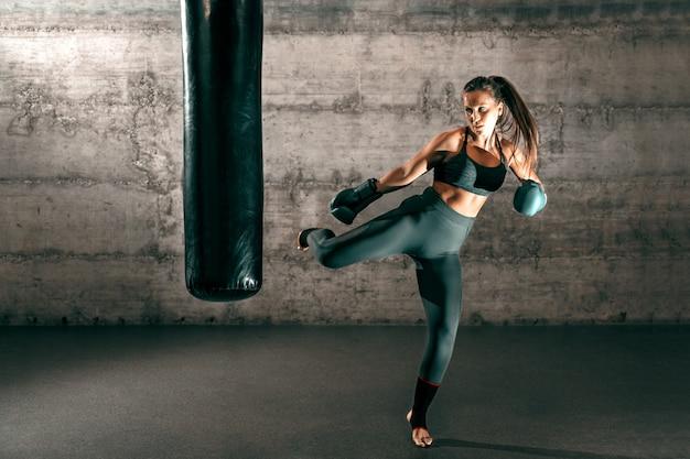 Bruna forte dedicata con coda di cavallo, in abbigliamento sportivo, piedi nudi e guantoni da boxe che calciano sacco in palestra. Foto Premium