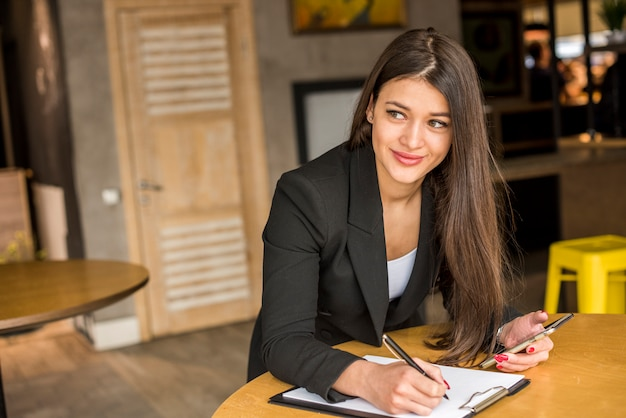 Bruna imprenditrice scrivendo su un documento Foto Gratuite