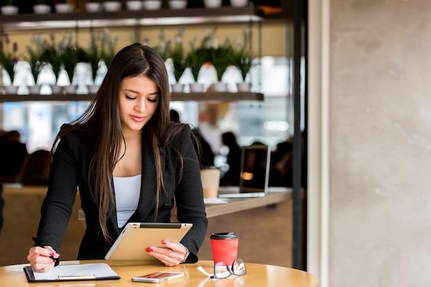 Bruna imprenditrice usando il suo tablet Foto Gratuite