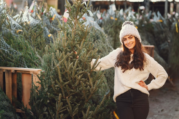 Brunetta carina in un maglione bianco con albero di natale Foto Gratuite