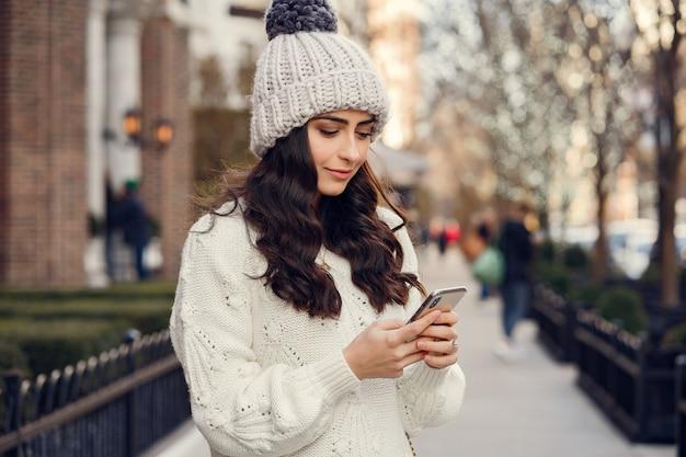 Brunetta carina in un maglione bianco in una città Foto Gratuite