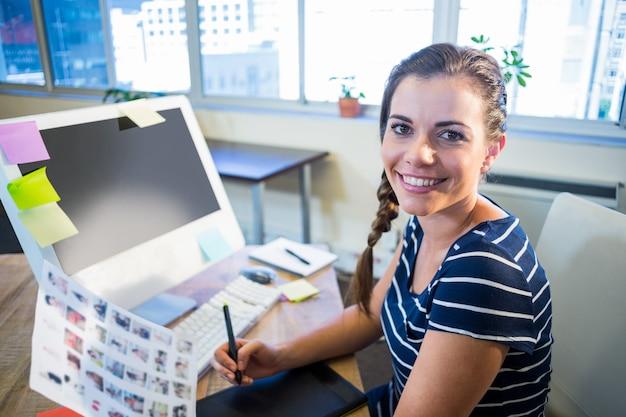 Brunette sorridente che lavora con le fotografie e il convertitore analogico / digitale Foto Premium