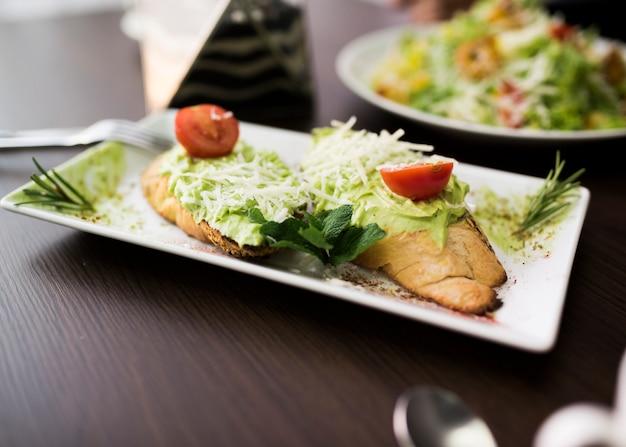 Bruschetta con pesto; formaggio grattugiato e pomodorini sul piatto Foto Gratuite