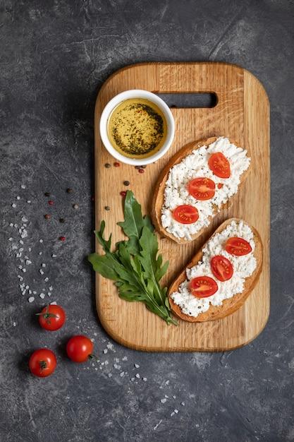 Bruschetta con pomodori arrostiti e mozzarella su un tagliere Foto Premium