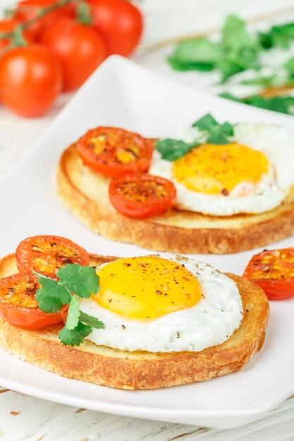Bruschetta con uovo fritto, pomodori ed erbe Foto Premium