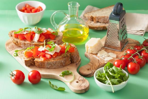 Bruschetta italiana con rucola di parmigiano di pomodori Foto Premium