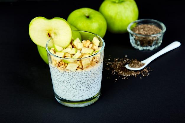 Budino di chia sano con mele e muesli in vetro. Foto Premium