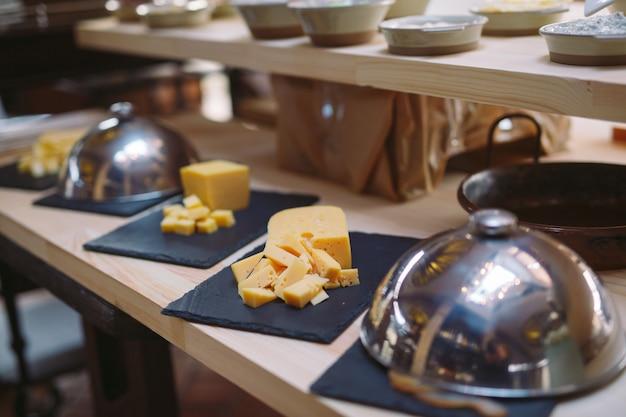 Buffet. il cameriere tiene un piatto di formaggio a fette. Foto Premium