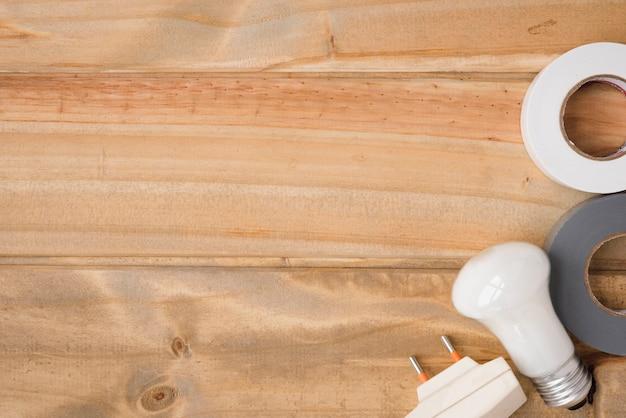 Bulbo bianco; nastro isolante e pulsante sul tavolo di legno Foto Gratuite