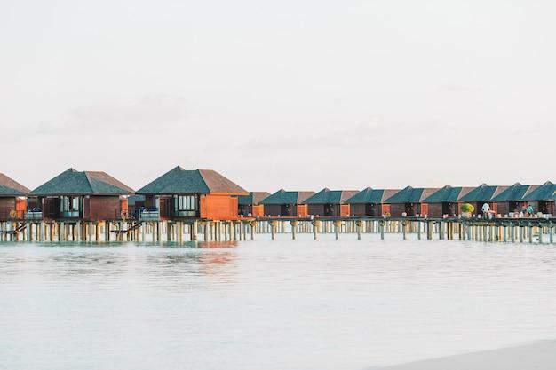Bungalow sull'acqua con acqua turchese sulle maldive Foto Premium