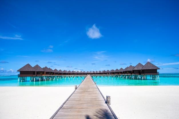 Bungalow sull'acqua e pontile in legno alle maldive Foto Premium
