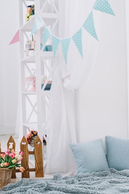 Bunting sul letto con cesto di tulipani; recinzione; coperta di pelliccia e cuscino a casa Foto Gratuite