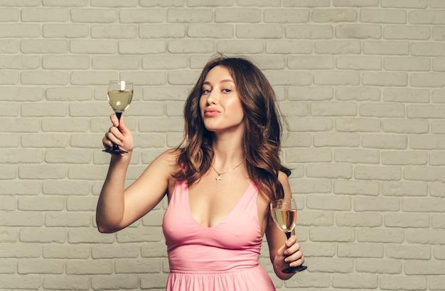 Buon anno a te. una giovane e bella donna che balla con un bicchiere di champagne Foto Premium