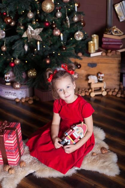 . buon natale, buone vacanze. la bambina in un vestito rosso tiene un giocattolo di schiaccianoci di legno d'annata vicino ad un albero di natale classico a casa. ballerina con lo schiaccianoci alla vigilia di superficie. Foto Premium