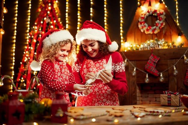 Buon natale e buone feste. bambina riccia sveglia allegra e sua sorella maggiore in cappelli di santa che cucinano i biscotti di natale. Foto Premium