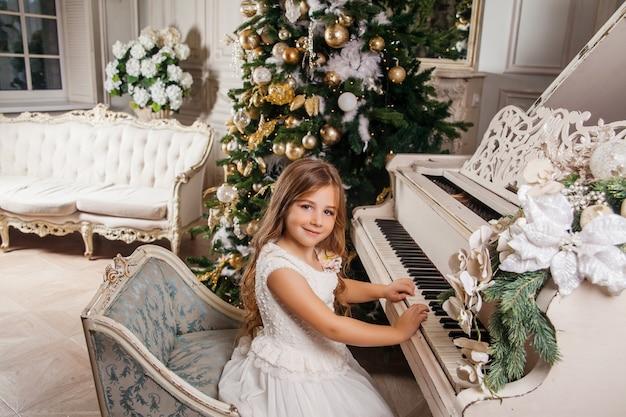 Buon natale e buone feste. la bambina sveglia nell'interiore classico bianco che gioca su un piano bianco ha decorato l'albero di natale. nuovo anno Foto Premium
