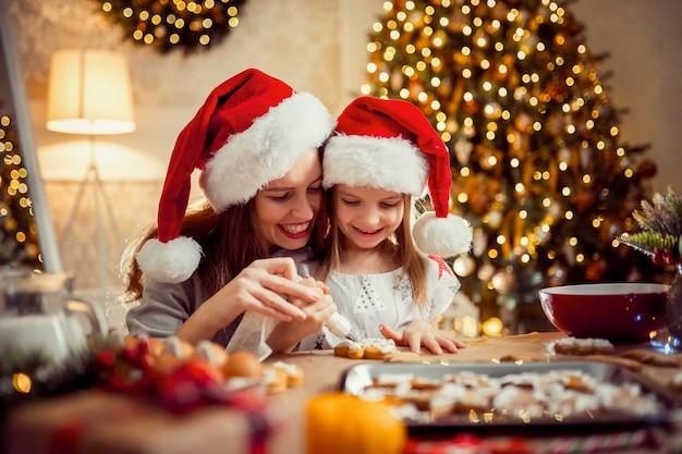 Buon natale e buone feste. madre e figlia che cucinano i biscotti di natale. Foto Premium