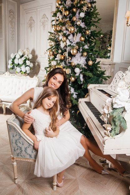 Buon natale e buone feste. mamma allegra e sua figlia carina ragazza in bianco classico interno bianco piano e un albero di natale decorato. nuovo anno Foto Premium