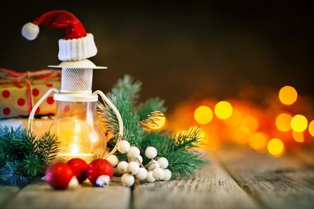Buon natale e felice anno nuovo. candela e giocattoli di natale su un tavolo di legno sul tavolo di una ghirlanda. bokeh. messa a fuoco selettiva. sfondo Foto Premium