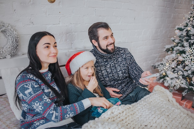 Buon natale e felice anno nuovo . giovane famiglia che celebra la vacanza a casa. il padre tiene il telecomando dalla tv. papà, figlia e madre guardano la televisione. Foto Premium