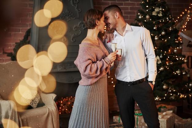 Buon passatempo. belle coppie che celebrano il nuovo anno davanti all'albero di natale Foto Premium