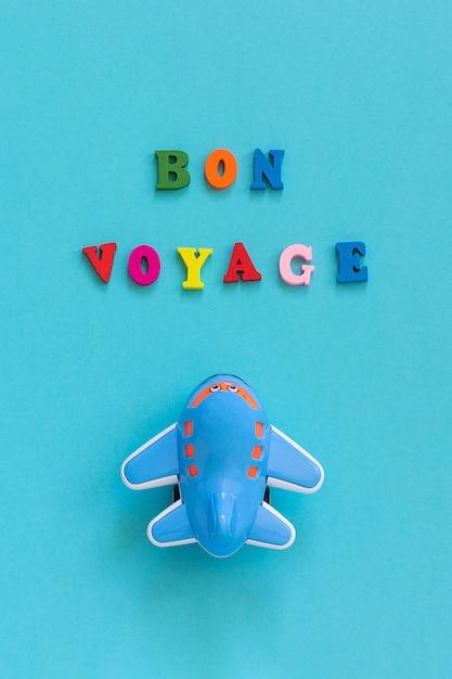 Buon viaggio e divertente giocattolo aereo per bambini su sfondo blu. concetto di viaggio, turismo Foto Premium