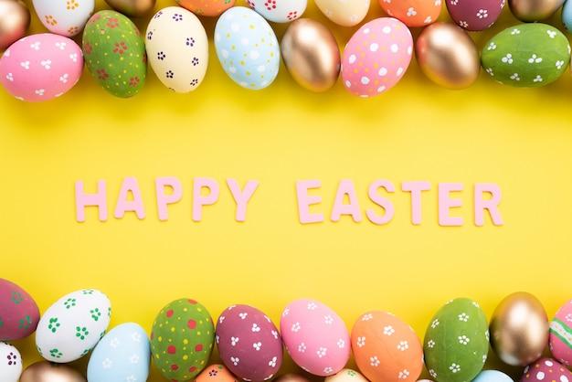 Buona pasqua! chiuda sulle uova di pasqua variopinte su fondo di carta giallo Foto Premium