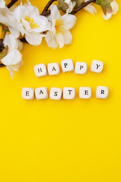 Buona pasqua. cubi con testo su sfondo giallo. brunch di primavera con fiori bianchi. posa piatta minimalista. Foto Premium