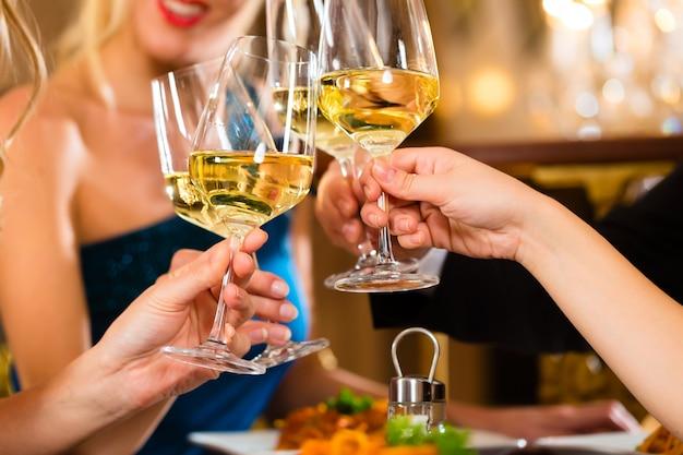 Buoni amici per cena o pranzo in un raffinato ristorante, bicchieri tintinnanti Foto Premium