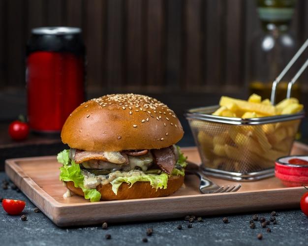 Burger panino ripieno di carne e verdure e servito in un vassoio con patate. Foto Gratuite