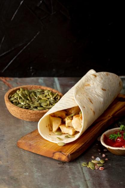 Burrito su tavola di legno vicino a salsa di pomodoro e cardamomo Foto Gratuite