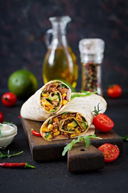 Burritos impacchi con carne e verdure su sfondo nero. burrito di manzo, cibo messicano. Foto Premium