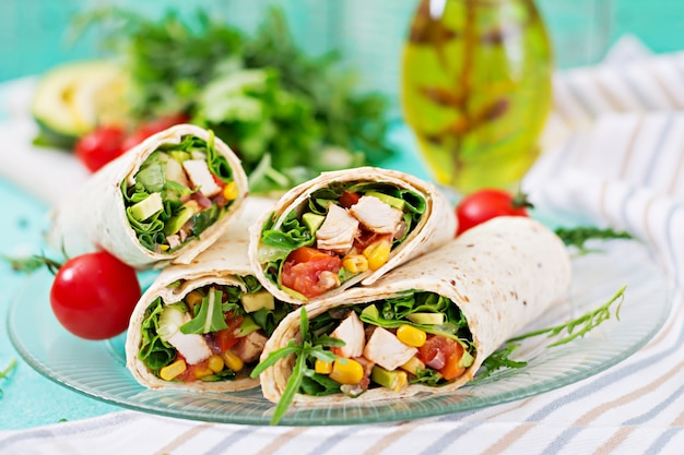 Burritos impacchi con pollo e verdure su sfondo chiaro. burrito di pollo Foto Premium