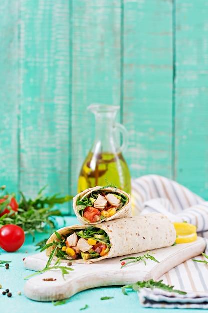 Burritos impacchi con pollo e verdure su sfondo chiaro. Foto Premium