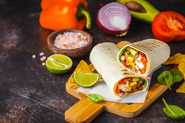 Burritos impacchi con pollo, fagioli, mais, pomodori e avocado su tavola di legno, sfondo scuro. Foto Premium