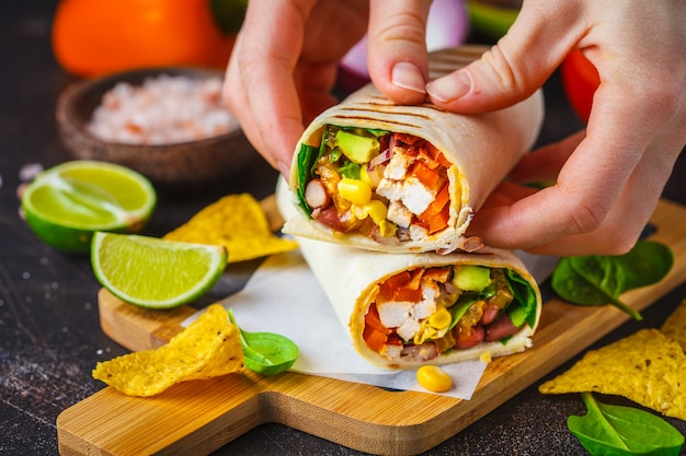Burritos impacchi con pollo, fagioli, mais, pomodori e avocado su tavola di legno Foto Premium