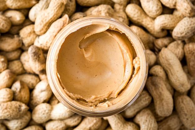 Burro di arachidi cremoso sulla superficie dell'arachide panoramica Foto Premium