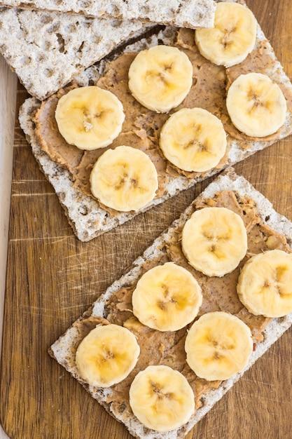 Burro di arachidi vegan sano e sandwich di banana con pane croccante integrale svedese Foto Premium