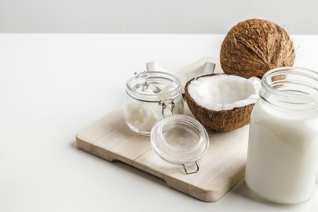 Burro di cocco sano organico e pezzi freschi della noce di cocco sul bordo di legno Foto Premium