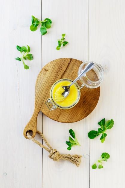 Burro di ghi con verdure su un tavolo di legno chiaro. orientamento verticale, vista dall'alto. Foto Premium