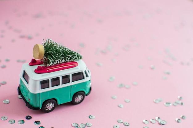 Bus del hippie con l'albero di abete di natale del nuovo anno sul tema del partito dell'insegna della piccola automobile miniatura del tetto Foto Premium