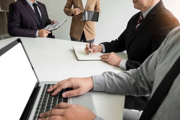 Business donna discutendo grafico finanziario su un touch pad dando una classe di formazione aziendale a un gruppo di giovani imprenditori in giro Foto Premium