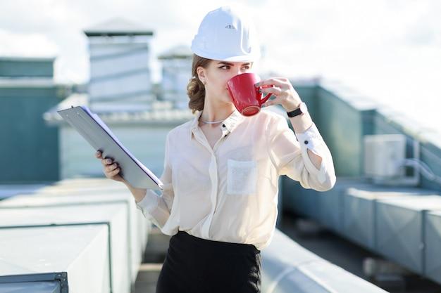 Businesslady attraente in camicetta bianca, orologio, casco e gonna nera stanno sul tetto e tengono tablet e tazza di caffè Foto Premium