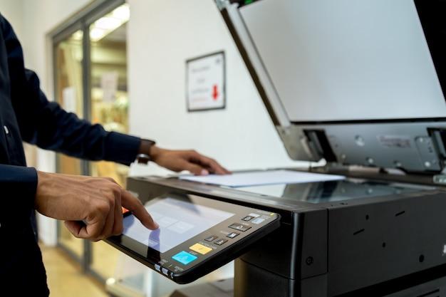 Bussiness man mano premere il pulsante sul pannello della stampante, stampante laser scanner ufficio macchina copia inizio concetto. Foto Premium