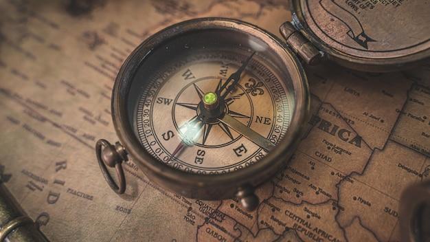 Bussola d'epoca sulla mappa del vecchio mondo Foto Premium